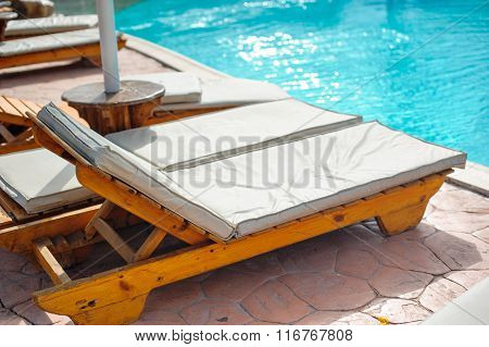 Wooden bed beside the pool. The beds are arranged behind the pool's edge