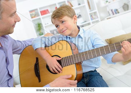 Young boy playing guitar to father