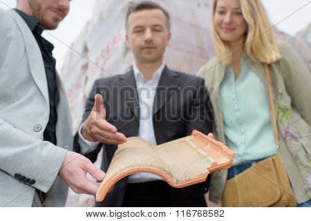 Salesman showing couple a modern rooftile