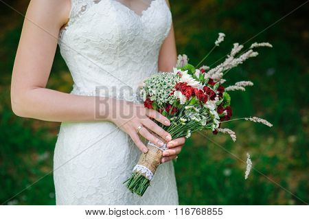 Bride Holding A Wedding Bouquet Of Wildflowers