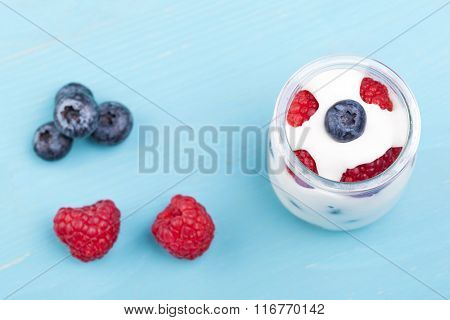 Glass of yogurt with berries and blueberries on a turquoise wooden table
