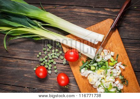 sliced fresh leek on wooden board with tomatoes