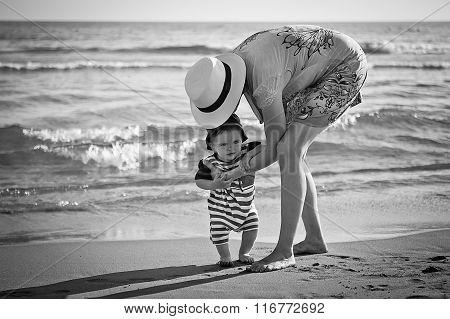 Mom Teaches A Baby To Walk On The Beach
