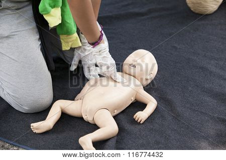 Infant dummy cardiac massage. First aid training.