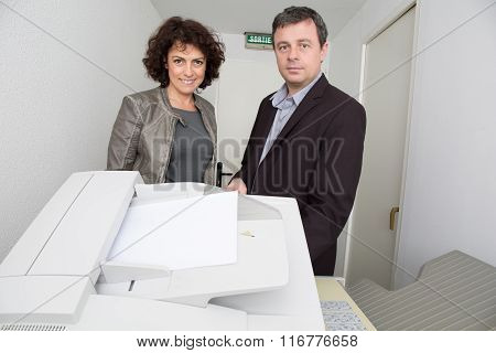 Middle Aged Man And Woman With Photocopy