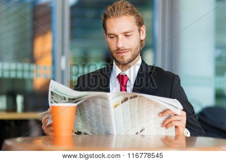 Handsome man with newspaper and coffee