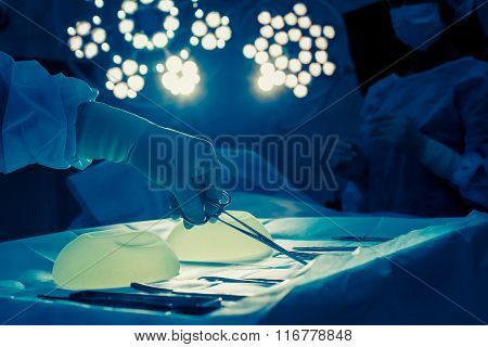 Nurse hand taking surgical instrument for group of surgeons at b