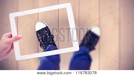 Masculine hand holding tablet against wooden planks