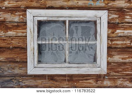 Frozen window in blockhouse wall. icicle. frost texture. New wood wall