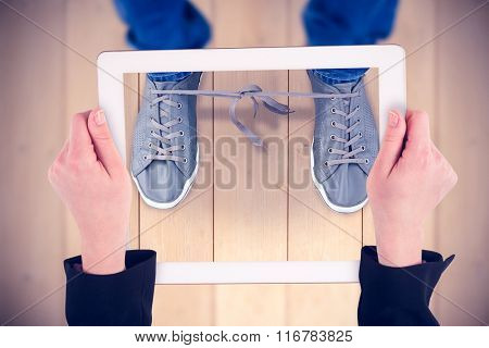 Feminine hands holding tablet against wooden planks