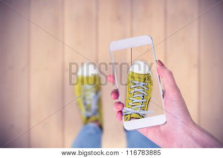 Hand holding smartphone against wooden planks