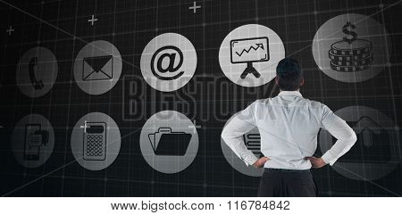 Businessman standing back to the camera with hands on hips against blue matrix