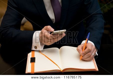 Man working at the office with notebook and cellphone