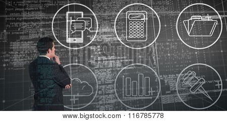 Businessman standing and looking against blue matrix and codes