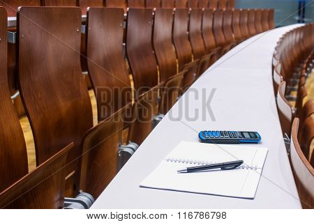 Notebook, Pen And Calculator In Empty University Lecture Room