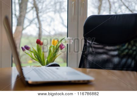 Laptop in front of the window with flowers