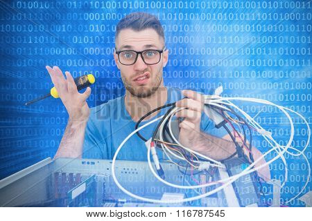 Portrait of confused it professional with screw driver and cables in front of open cpu against glowing futuristic binary code