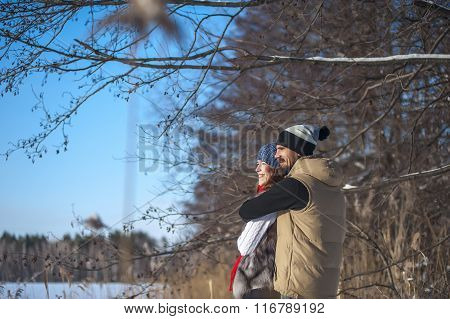 Bearded Man and woman are hugging smiling young family hugging in the fresh winter air. Happy relati