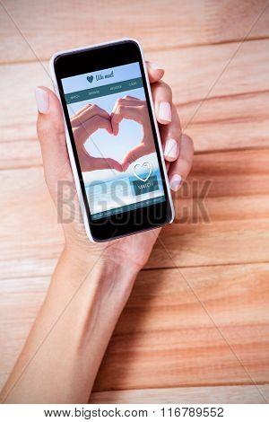 Dating website against feminine hand holding smartphone