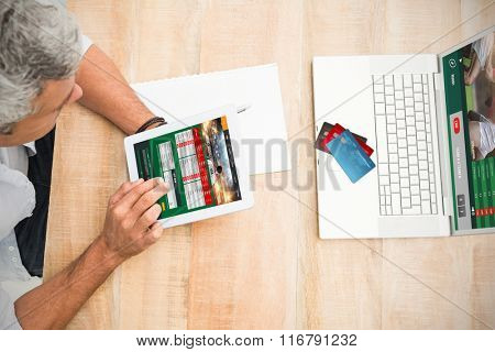 Colorful world credit cards against casual businessman using blank screen tablet