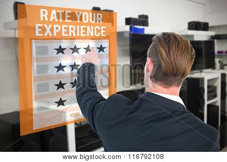 Rear view of young businessman in suit pointing against telephone test app