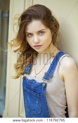 Portrait of a young girl in denim overalls, close up