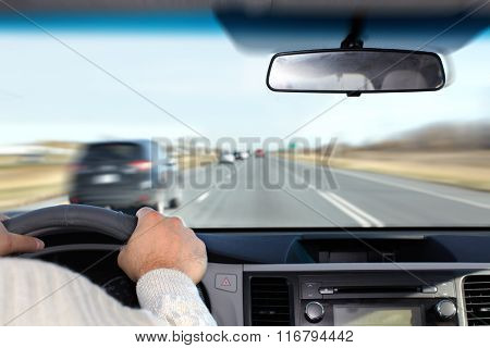 Hand of man driving on a highway.