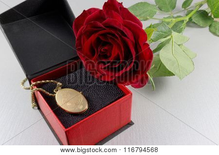 Red rose and golden locket in a gift box