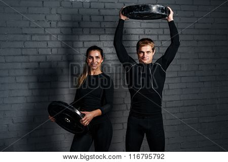 Strong man an sporty woman in gym