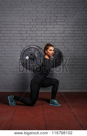 Woman with barbell doing split squat or lunge