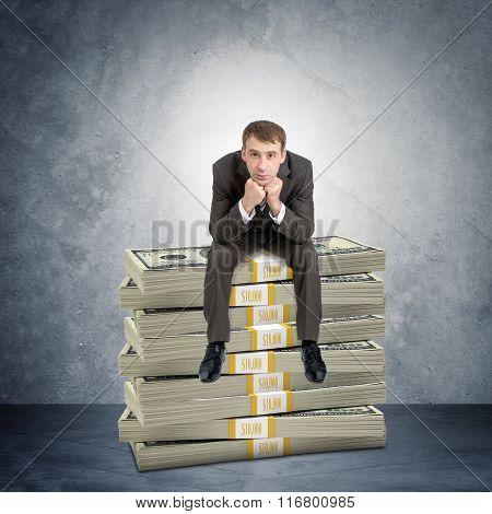 Businessman sitting on cash