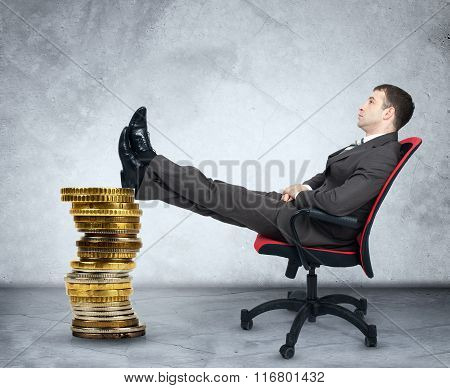 Businessman sitting on chair and pile of coins