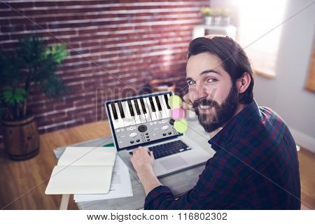Music app against portrait of smiling editor using laptop