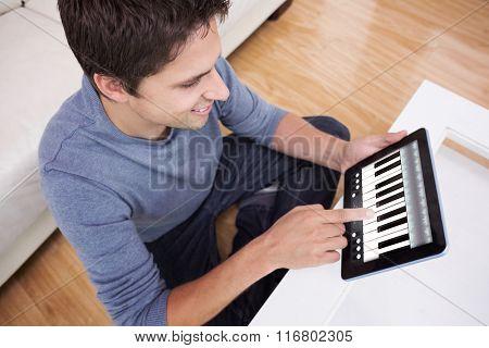 Overhead view of man using digital tablet in living room against music app