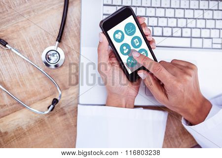 Medical app against doctor using smartphone on wooden desk