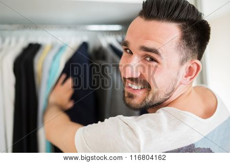 Smiling Man Choosing Clothes