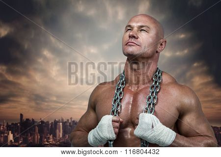 Confident bodybuilder holding chain while looking up against dusty path leading to large city