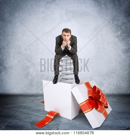 Businessman sitting on coil spring