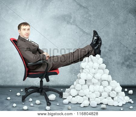 Businessman and pile crumpled paper balls