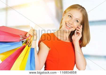 Happy Woman With  Bags On Shopping And Kredit Card Talking On Phone