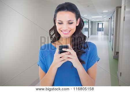Pretty brunette sending a text against college hallway