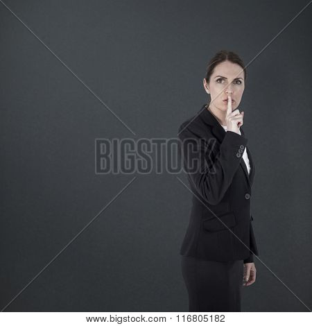 Businesswoman asking for silence over white background against grey background