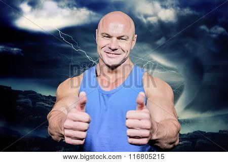 Smiling healthy man showing thumbs up against stormy sky with tornado over landscape