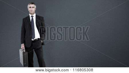 Businessman crossing finish line and cheering against grey background