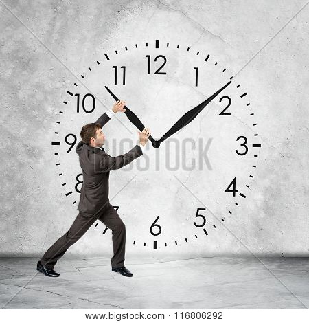 Businessman holding clock hand