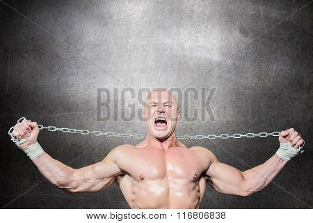 Fighter holding chain with arms raised against black wall