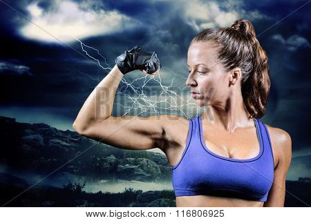 Confident woman flexing muscles against stormy sky with tornado over landscape