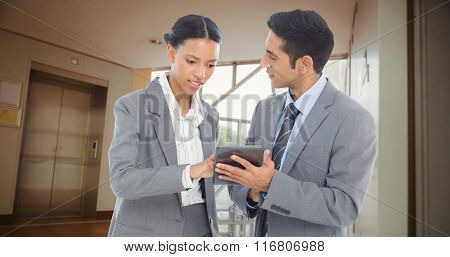 Business people discussing over digital tablet against foyer area with elevator