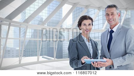 Business team using tablet pc against modern room overlooking city