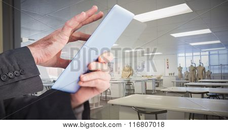 Businessman scrolling on his digital tablet against empty class room